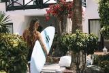Mädel mit Surfbrett vor Unterkunft in Fuerteventura